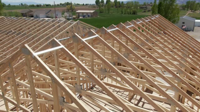 descending aerial drone shot of a row of wooden roof trusses of a framed house on a construction site with construction workers on a sunny day - строить стоковые видео и кадры b-roll