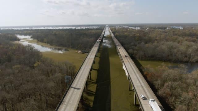 vidéos et rushes de descendants de drone aérien coup de volant à côté de breaux bridge (interstate 10) avec salvinia flottant sur la rivière atchafalaya basin marais entouré de forêts de cyprès dans le sud de la louisiane sous un ciel ensoleillé mais partiellement nu - route surélevée