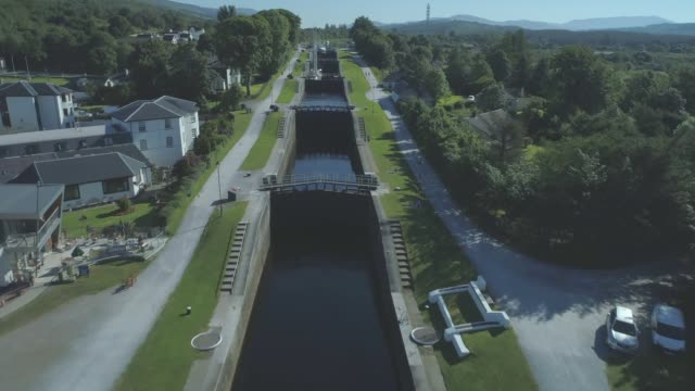 descending aerial travelling down the neptune's staircase series of locks on the caledonian canal in banavie, fort william, scotland - fort william video stock e b–roll