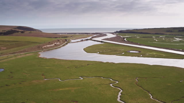 descending drone shot of the river cuckmere draining into the english channel - south downs video stock e b–roll