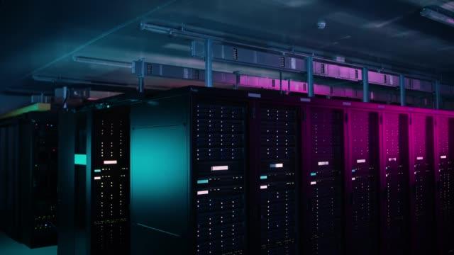 fallande skott av datacenter med flera rader av fullt fungerande serverrack. modern telekommunikation, cloud computing, artificiell intelligens, databas, superdator teknik koncept. skott i mörkret med neon blå, rosa lyser. - server room bildbanksvideor och videomaterial från bakom kulisserna