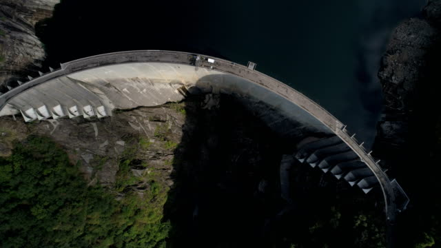 descent to foot of contra barrage - aerial 4k - bungee jumping video stock e b–roll