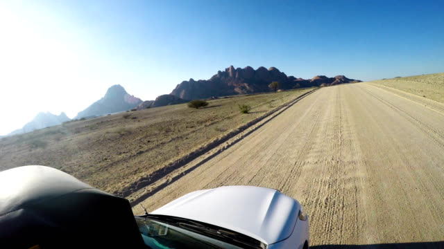 Desert adventure Driver's POV. Road trip on a desert. Namibia, spitzkoppe. namibia stock videos & royalty-free footage