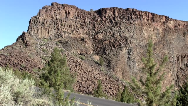 Desert jagged cliff formation near road zoom out video