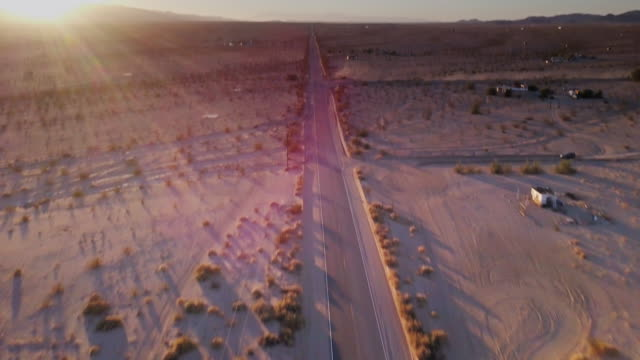 Desert Road at Dusk - Drone Shot Drone flight over a road across open desert near Twentynine Palms, California, beginning looking straight down and panning up to take in the arid landscape and the sun about to set behind the bare hills. mojave desert stock videos & royalty-free footage