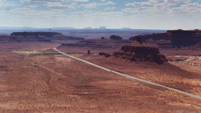 Desert Road with Monument Valley Silhouetted in Distance - vídeo