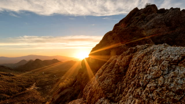 Desert Sunrise Timelapse/Hyperlapse - View 18 Timelapse of a partly cloudy desert sunrise viewed from a mountain pass.  Shot in HDR.  Includes hyperlapse sliding motion past rocks and in the foreground. sunrise dawn stock videos & royalty-free footage