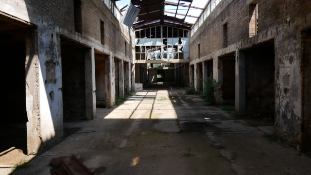 Deserted ruins of old factory - broken windows and demolished interior