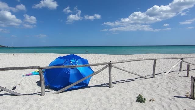 Deserted white beach with a blue beach umbrella seen from behind that flutters in the wind against a background of blue sea and sky