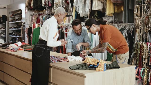 vídeos y material grabado en eventos de stock de profesionales del diseño analizando textil en estudio - moda preppy