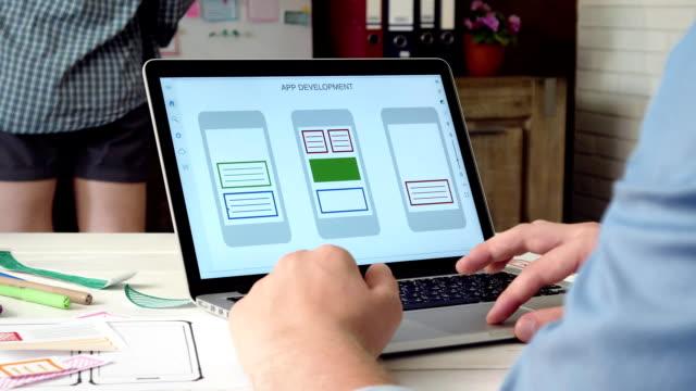 ux-designer erstellen mobile app prototyp auf seinem laptopcomputer - reisebüro stock-videos und b-roll-filmmaterial