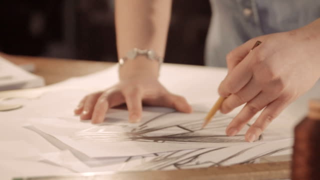 Designer draws a line on the paper. Women drawing and paint. close up video