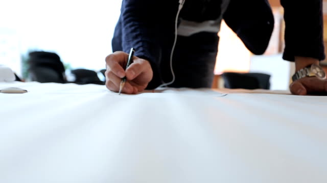 Designer in black jacket masterfully creates draft on sheet of paper video