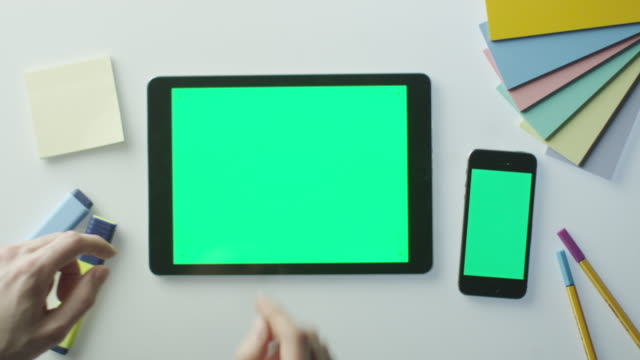 Designer is Using Tablet and Mobile Phone with Green Screen. Great For Mock-up Usage. Shot on RED Cinema Camera video