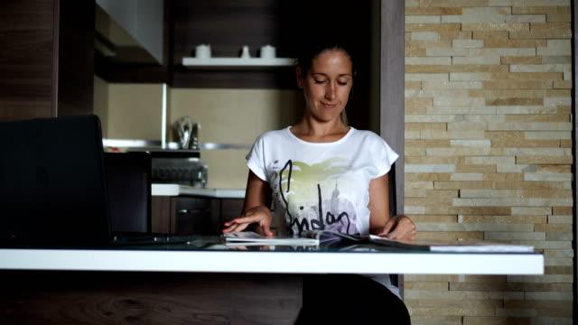 stockvideo's en b-roll-footage met ontwerper op zoek naar ideeën in magazine - woman home magazine