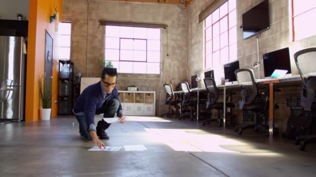 Designer Plans Layout On Floor Of Modern Office Shot On R3D video