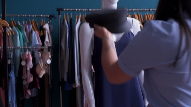 designer putting a hat on dummy head video