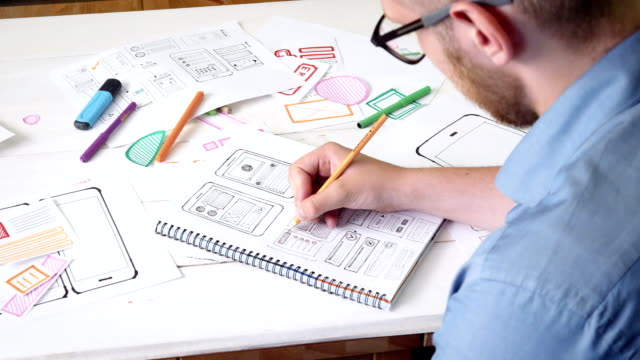 ux designer sketching prototype of a new app in his notebook - designers video stock e b–roll