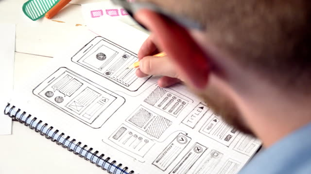 vídeos de stock e filmes b-roll de ux designer sketching prototype of a new app in his notebook - design