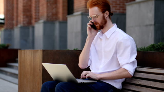 Designer Talking on Phone while Sitting on Bench, Discussing video