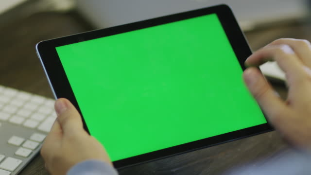 designer using digital tablet with green screen in landscape mode at work. - tablet stock videos and b-roll footage