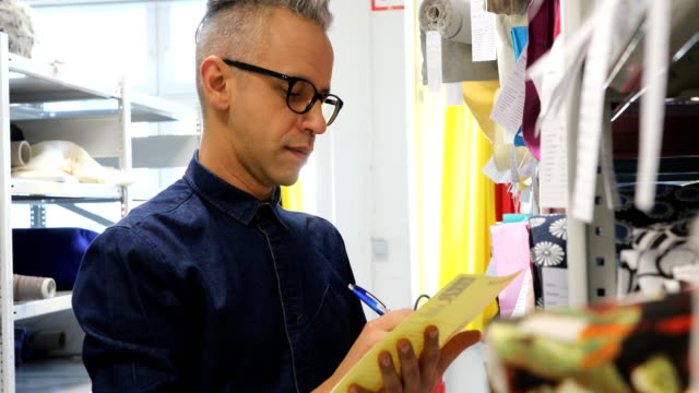 Designer writing on checklist by textile rack Confident male manager writing on checklist while looking at labels. Fashion designer is examining fabrics in rack. He is working at textile shop. stationary stock videos & royalty-free footage