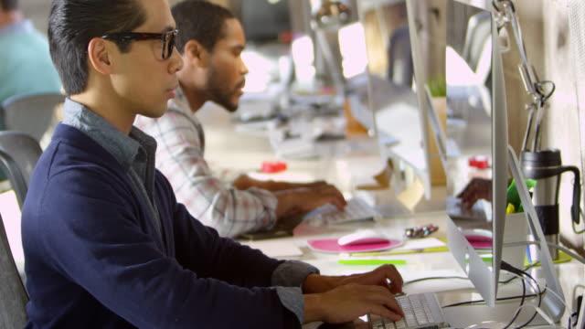 vídeos de stock e filmes b-roll de designers trabalhando em computadores no escritório moderno em r3d filmagem - cool