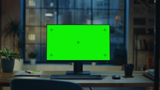 현대 창조적 인 사무실에서 나무 책상에 서 있는 모형 녹색 화면이있는 데스크톱 컴퓨터. 배경 따뜻한 저녁 조명과 도시 창보기와 열린 공간 스튜디오에서. 확대/축소 샷 - 책상 스톡 비디오 및 b-롤 화면