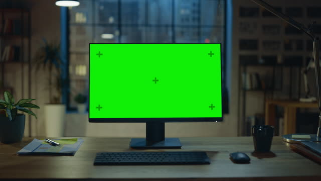 Desktop Computer with Mock-up Green Screen Standing on the Wooden Desk in the Modern Creative Office. In the Background Warm Evening Lighting and Open Space Studio with City Window View. Zoom Out Shot