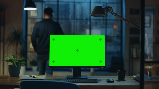 Desktop Computer with Mock-up Green Screen Standing on the Wooden Desk in the Modern Creative Office. In the Background Designer Drinks from a Cup Looks at the Night City out of the Window