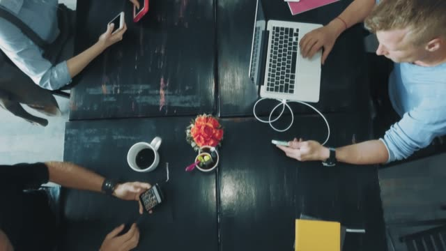 Desktop of a creative business team that works on laptops and communicates using smartphones in office. Coworking. Top view Desktop of a creative business team that works on laptops and communicates using smartphones in office. Coworking. Top view. coworking stock videos & royalty-free footage