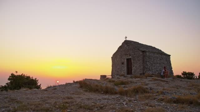 SLO MO Despair woman by a stone chapel video
