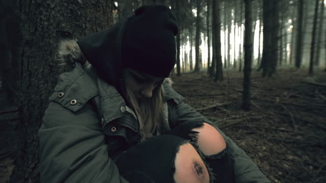 Despaired young woman sitting in the forest video