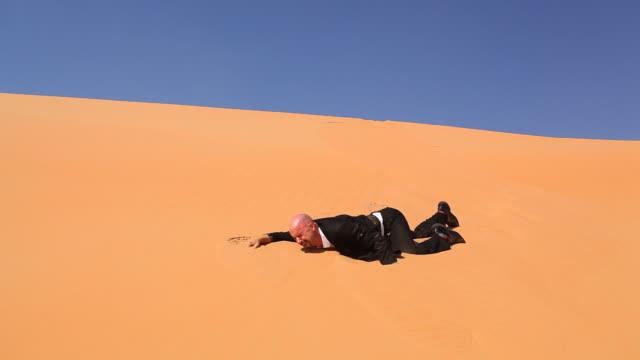 desperate businessman in desert dunes thirsty part II video
