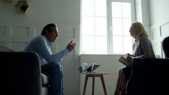 desperate man sharing his problems with psychologist - therapist filmów i materiałów b-roll