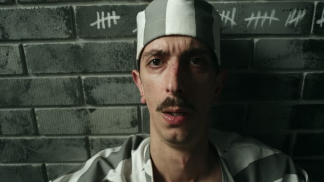 Desperate  men sitting on floor at prison cell video