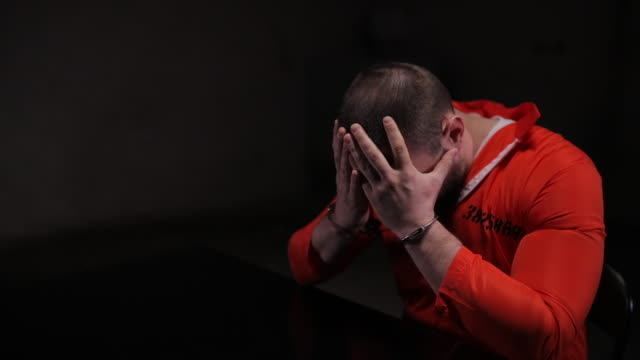 desperate prisoner in orange jumpsuit sitting alone in interrogation room - наручники стоковые видео и кадры b-roll