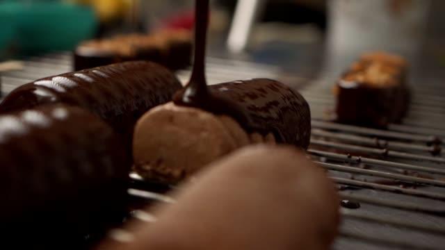 vídeos y material grabado en eventos de stock de chef de postres cubriendo una galleta de pastel en una paleta con un chocolate negro derretido en una bandeja de red de metal - galleta dulces
