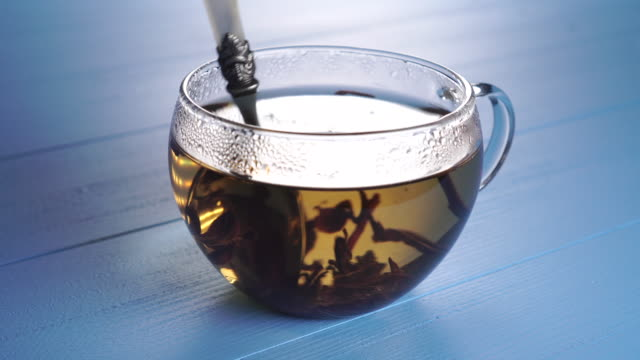 Dessert spoon stirs the petals of herbal tea in a glass cup on a blue wooden background