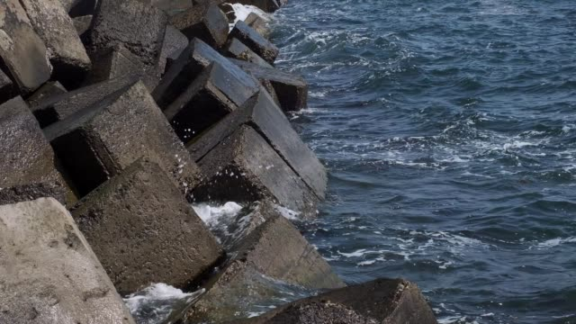 Destroyed coastal concrete protective structure. Large deep cracks between slabs of blocks protect shore from erosion of impact of sea wave. Huge pieces of concrete with reinforcement to protect shore, Close-up, Full HD - 60fps