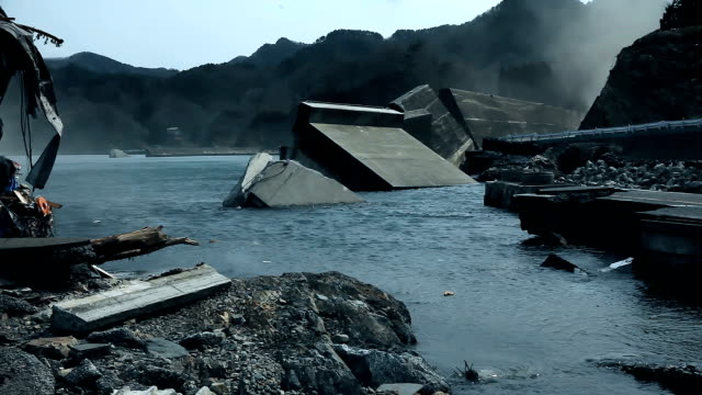 Destroyed harbour after the tsumani, dust flying everywhere Destroyed boat and port after the tsunami in Japan. City of Fukushima is ravaged after the disaster. No one in the town, an evacuate city. A lot of dust and trash. earthquake stock videos & royalty-free footage