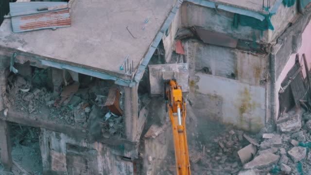 vídeos de stock e filmes b-roll de destroying old house using bucket excavator on construction site. slow motion - berlin wall