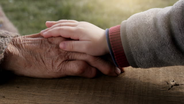 A HELPING HAND. Detail of a Child Hands Holding the Senior Woman Hands video