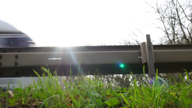 detail of a plant at the road with big traffic. with sound. shot with dolly. - parapetto barriera video stock e b–roll