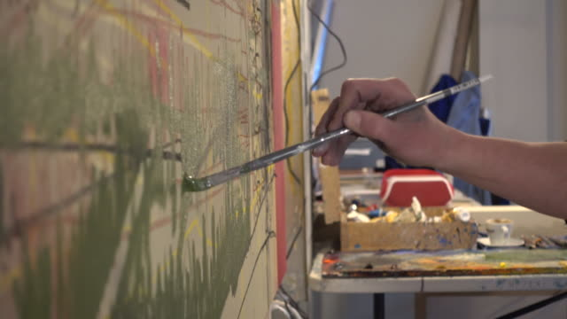 Detail of artist painting canvas, in studio video