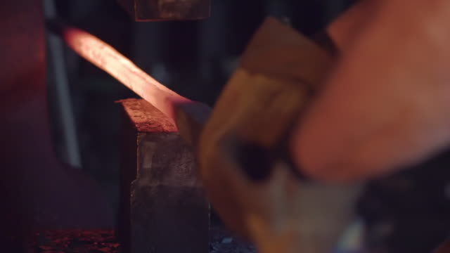 Detail of blacksmith using industrial hammer to shape hot metal video