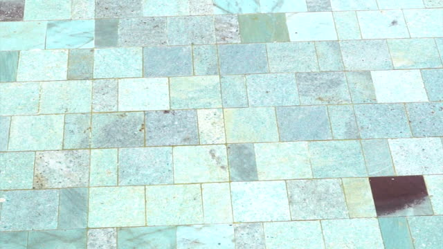 detail of clear swimming pool with water and natural stone tile floor video