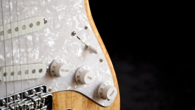 Detail of controls and strings of electric guitar turning video