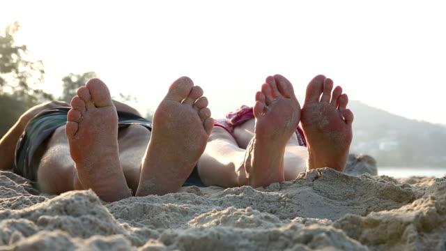 detail of couple's feet on empty beach, view from sand - sarong bildbanksvideor och videomaterial från bakom kulisserna