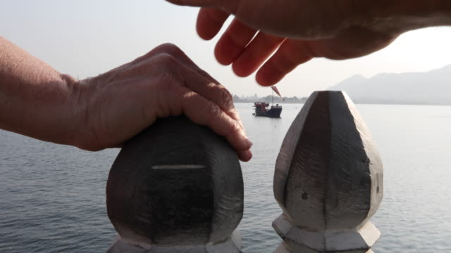 Detail of couple's hand on post above lake and floating palace